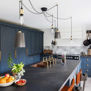 This is an example of a large urban l-shaped kitchen/diner in Essex with a double-bowl sink, shaker cabinets, blue cabinets, composite countertops, multi-coloured splashback, ceramic splashback, black appliances, porcelain flooring, an island, grey floors and black worktops.