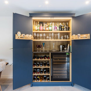 Inspiration for a large industrial l-shaped eat-in kitchen in Essex with a double-bowl sink, shaker cabinets, blue cabinets, solid surface benchtops, multi-coloured splashback, ceramic splashback, black appliances, porcelain floors, with island, grey floor and black benchtop.