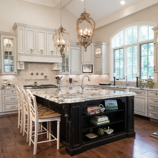 Huge elegant dark wood floor and brown floor open concept kitchen photo in Other with raised-panel cabinets, white cabinets, beige backsplash, an island, an undermount sink, granite countertops and stainless steel appliances