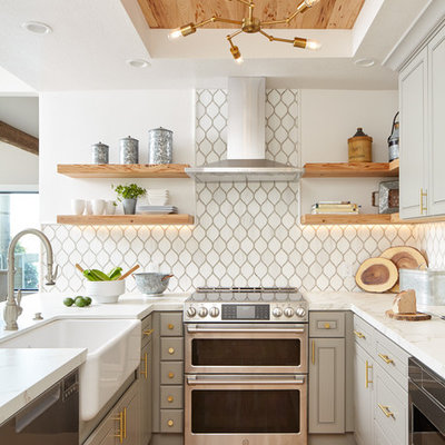 Beach style u-shaped light wood floor and beige floor kitchen photo in San Francisco with a farmhouse sink, recessed-panel cabinets, gray cabinets, white backsplash, stainless steel appliances, a peninsula, white countertops, marble countertops and ceramic backsplash