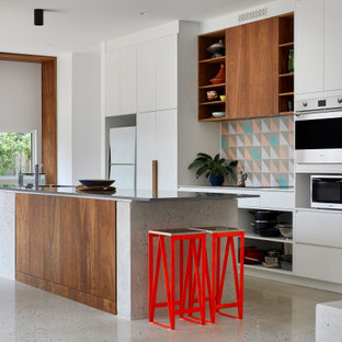 Photo of a mid-sized scandinavian galley open plan kitchen in Melbourne with a double-bowl sink, white cabinets, quartz benchtops, cement tile splashback, stainless steel appliances, concrete floors, with island, grey floor and grey benchtop.