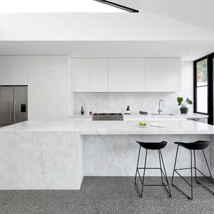 Photo of a large contemporary kitchen in Melbourne with an undermount sink, white cabinets, marble benchtops, white splashback, marble splashback, stainless steel appliances, concrete floors, with island, grey floor, white benchtop and flat-panel cabinets.