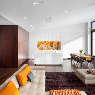 Modelo de cocina minimalista, abierta, con armarios con paneles lisos, puertas de armario blancas, salpicadero naranja, salpicadero de losas de piedra y electrodomésticos con paneles