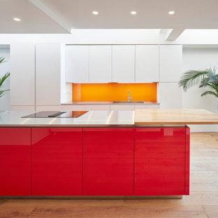 ロンドンの広いコンテンポラリースタイルのおしゃれなキッチン (一体型シンク、フラットパネル扉のキャビネット、赤いキャビネット、ステンレスカウンター、オレンジのキッチンパネル、ガラス板のキッチンパネル、パネルと同色の調理設備、淡色無垢フローリング、ベージュの床、グレーのキッチンカウンター) の写真