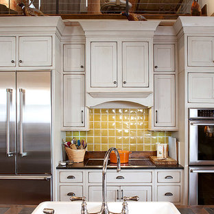 This is an example of a country eat-in kitchen in Other with a farmhouse sink, beaded inset cabinets, green cabinets, limestone benchtops, yellow splashback and stainless steel appliances.