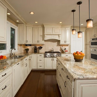 Large traditional u-shaped eat-in kitchen in DC Metro with a double-bowl sink, raised-panel cabinets, beige splashback, panelled appliances, granite benchtops, stone tile splashback, with island, beige cabinets and dark hardwood floors.