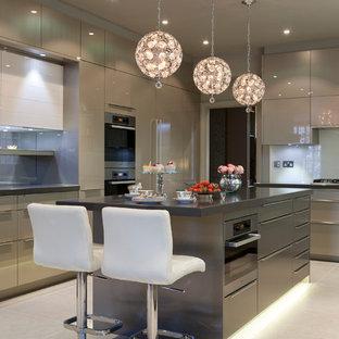 ロンドンの広いコンテンポラリースタイルのおしゃれなキッチン (フラットパネル扉のキャビネット、シルバーの調理設備、セラミックタイルの床、グレーのキャビネット、ガラス板のキッチンパネル) の写真