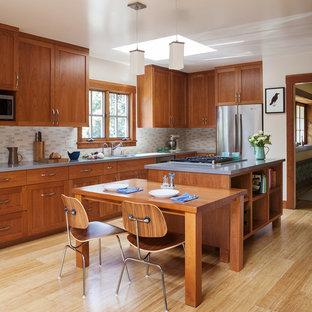 Cette image montre une cuisine américaine craftsman en U de taille moyenne avec un placard à porte shaker, des portes de placard en bois brun, un électroménager en acier inoxydable, un îlot central, un plan de travail en quartz modifié, une crédence beige, une crédence en carreau de céramique, un sol en bambou et un sol beige.