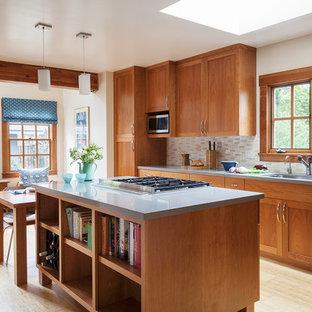 Cette photo montre une cuisine américaine chic en U de taille moyenne avec un évier 1 bac, un placard à porte shaker, des portes de placard en bois brun, un plan de travail en quartz modifié, une crédence beige, une crédence en carreau de céramique, un électroménager en acier inoxydable, un îlot central, un sol en bambou et un sol beige.