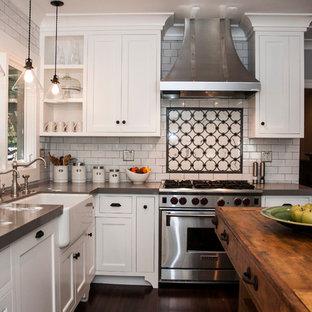 ロサンゼルスの中サイズのエクレクティックスタイルのおしゃれなキッチン (エプロンフロントシンク、シェーカースタイル扉のキャビネット、白いキャビネット、クオーツストーンカウンター、白いキッチンパネル、サブウェイタイルのキッチンパネル、シルバーの調理設備の、濃色無垢フローリング、茶色い床、グレーのキッチンカウンター) の写真