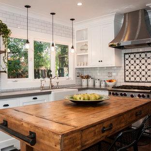 ロサンゼルスの中サイズのエクレクティックスタイルのおしゃれなキッチン (エプロンフロントシンク、シェーカースタイル扉のキャビネット、白いキャビネット、クオーツストーンカウンター、白いキッチンパネル、サブウェイタイルのキッチンパネル、濃色無垢フローリング、シルバーの調理設備の、茶色い床、グレーのキッチンカウンター) の写真
