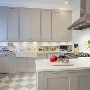 Transitional kitchen inspiration - Inspiration for a transitional u-shaped kitchen remodel in Boston with a farmhouse sink, shaker cabinets, gray cabinets, white backsplash, subway tile backsplash and a peninsula
