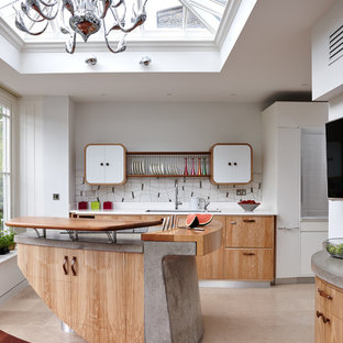 Large trendy beige floor kitchen photo in London with an undermount sink, flat-panel cabinets, light wood cabinets, white backsplash and an island