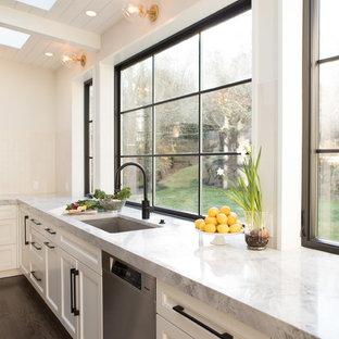 シアトルの広いコンテンポラリースタイルのおしゃれなキッチン (アンダーカウンターシンク、落し込みパネル扉のキャビネット、白いキャビネット、珪岩カウンター、白いキッチンパネル、セラミックタイルのキッチンパネル、シルバーの調理設備、無垢フローリング、茶色い床、グレーのキッチンカウンター) の写真
