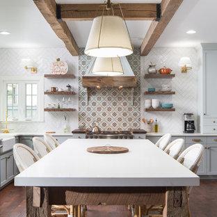 Esempio di una cucina a L costiera con lavello stile country, ante in stile shaker, ante grigie, paraspruzzi multicolore, elettrodomestici in acciaio inossidabile, parquet scuro, isola, pavimento marrone e top bianco