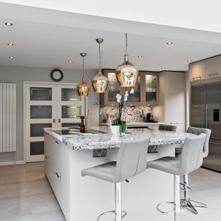 Contemporary kitchen in Berkshire with granite worktops, an island, flat-panel cabinets, grey cabinets, stainless steel appliances, grey floors and multicoloured worktops.