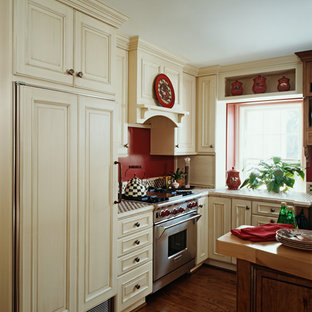 Farmhouse eat-in kitchen ideas - Inspiration for a country l-shaped medium tone wood floor eat-in kitchen remodel in Other with a farmhouse sink, raised-panel cabinets, tile countertops, red backsplash, paneled appliances and an island