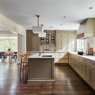 Large transitional l-shaped eat-in kitchen in Philadelphia with an undermount sink, marble benchtops, white splashback, porcelain splashback, stainless steel appliances, dark hardwood floors, with island, white benchtop, shaker cabinets, brown cabinets and brown floor.