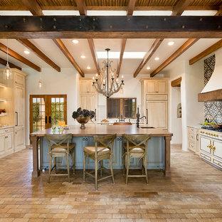 Exemple d'une cuisine avec un placard avec porte à panneau surélevé, des portes de placard beiges, une crédence multicolore, un électroménager encastrable, un sol en brique, un îlot central et un plan de travail gris.