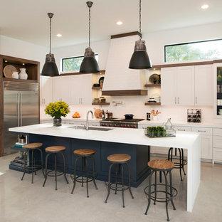 マイアミの中くらいのインダストリアルスタイルのおしゃれなキッチン (ダブルシンク、シェーカースタイル扉のキャビネット、ベージュのキャビネット、クオーツストーンカウンター、ベージュキッチンパネル、セラミックタイルのキッチンパネル、シルバーの調理設備、コンクリートの床) の写真