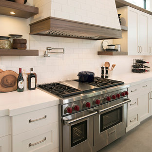 Mid-sized industrial l-shaped open plan kitchen in Miami with a double-bowl sink, shaker cabinets, beige cabinets, quartz benchtops, beige splashback, ceramic splashback, stainless steel appliances, concrete floors and with island.