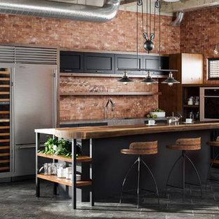 Imagen de cocina en L, industrial, abierta, con fregadero integrado, puertas de armario negras, encimera de madera, salpicadero rojo, salpicadero de ladrillos, electrodomésticos de acero inoxidable, suelo de baldosas de porcelana, una isla y armarios con paneles lisos
