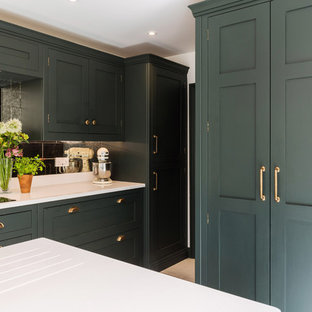 This is an example of a large traditional l-shaped eat-in kitchen in London with an integrated sink, shaker cabinets, green cabinets, quartzite benchtops, metallic splashback, glass tile splashback, panelled appliances, limestone floors, with island, white floor and white benchtop.