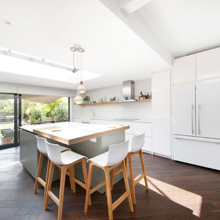 Photo of a large contemporary single-wall open plan kitchen in London with a belfast sink, flat-panel cabinets, white cabinets, quartz worktops, white splashback, matchstick tiled splashback, black appliances, dark hardwood flooring, an island, brown floors and white worktops.