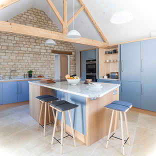 Inspiration for a medium sized scandi l-shaped kitchen in Wiltshire with a single-bowl sink, flat-panel cabinets, granite worktops, limestone flooring, an island, beige floors, blue cabinets and black appliances.