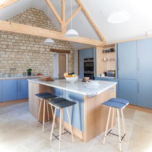 Mittelgroße Nordische Küche in L-Form mit Waschbecken, flächenbündigen Schrankfronten, Granit-Arbeitsplatte, Kalkstein, Kücheninsel, beigem Boden, blauen Schränken und schwarzen Elektrogeräten in Wiltshire