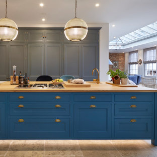 This is an example of a large traditional kitchen in London with a submerged sink, recessed-panel cabinets, wood worktops, an island, brown floors, beige worktops and blue cabinets.