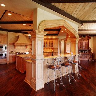 Offene, Große Mediterrane Küche in U-Form mit Schrankfronten mit vertiefter Füllung, beigen Schränken, Granit-Arbeitsplatte, Küchenrückwand in Beige, Rückwand aus Steinfliesen, Küchengeräten aus Edelstahl, dunklem Holzboden und Kücheninsel in Cedar Rapids
