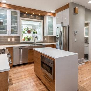 Foto på ett mellanstort funkis kök, med en rustik diskho, vita skåp, bänkskiva i kvarts, grått stänkskydd, stänkskydd i glaskakel, rostfria vitvaror, ljust trägolv, en köksö, släta luckor och beiget golv