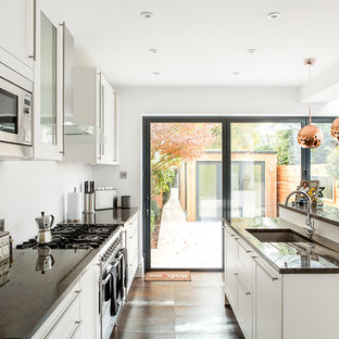 This is an example of a medium sized contemporary l-shaped open plan kitchen in London with white cabinets, a submerged sink, stainless steel appliances, brown floors, black worktops, an island, shaker cabinets and granite worktops.