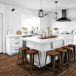 Пример оригинального дизайна интерьера: угловая кухня среднего размера в стиле кантри с обеденным столом, врезной раковиной, фасадами в стиле шейкер, белыми фасадами, столешницей из кварцита, белым фартуком, фартуком из плитки кабанчик, черной техникой, полом из винила, островом, коричневым полом и белой столешницей