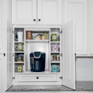 Klassisk inredning av ett stort kök och matrum, med granitbänkskiva, vitt stänkskydd, stänkskydd i tegel, rostfria vitvaror, mellanmörkt trägolv, en köksö, en dubbel diskho, luckor med infälld panel, vita skåp och brunt golv