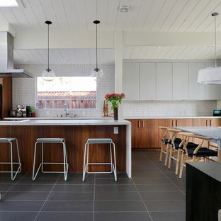 This is an example of a large midcentury galley eat-in kitchen in San Francisco with medium wood cabinets, white splashback, ceramic splashback, ceramic floors, a peninsula, grey floor and white benchtop.