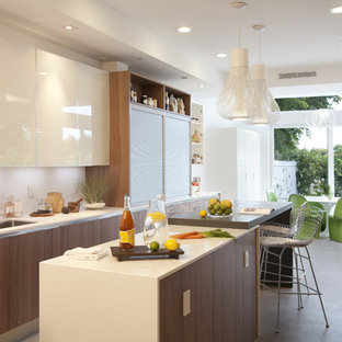 Modern eat-in kitchen in Miami with flat-panel cabinets and white cabinets.