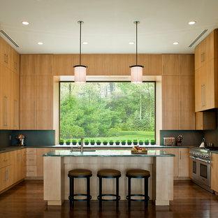 Idéer för ett modernt grön u-kök, med släta luckor, skåp i ljust trä, grönt stänkskydd och rostfria vitvaror