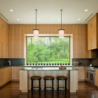 This is an example of a modern u-shaped kitchen in New York with flat-panel cabinets, light wood cabinets, green splashback, stainless steel appliances and green benchtop.