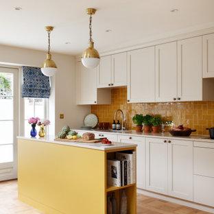 Modelo de cocina de galera, tradicional renovada, con fregadero bajoencimera, armarios estilo shaker, puertas de armario blancas, salpicadero naranja, suelo de madera clara, una isla, suelo beige y encimeras beige