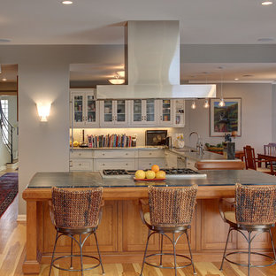 Traditional kitchen designs - Inspiration for a timeless u-shaped medium tone wood floor kitchen remodel in Indianapolis with glass-front cabinets, white cabinets and an island