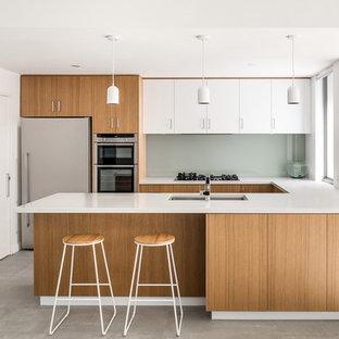 パースのモダンスタイルのおしゃれなキッチン (アンダーカウンターシンク、淡色木目調キャビネット、クオーツストーンカウンター、グレーのキッチンパネル、ガラス板のキッチンパネル、シルバーの調理設備の、セラミックタイルの床、グレーの床、白いキッチンカウンター) の写真