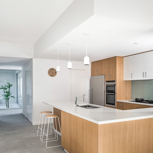 Inspiration for a contemporary u-shaped kitchen in Perth with light wood cabinets, quartz benchtops, glass sheet splashback, stainless steel appliances, ceramic floors, grey floor, white benchtop, a double-bowl sink, flat-panel cabinets, green splashback and a peninsula.