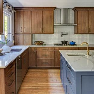 シカゴの大きいモダンスタイルのおしゃれなキッチン (アンダーカウンターシンク、フラットパネル扉のキャビネット、中間色木目調キャビネット、クオーツストーンカウンター、白いキッチンパネル、サブウェイタイルのキッチンパネル、シルバーの調理設備、無垢フローリング、茶色い床、白いキッチンカウンター) の写真
