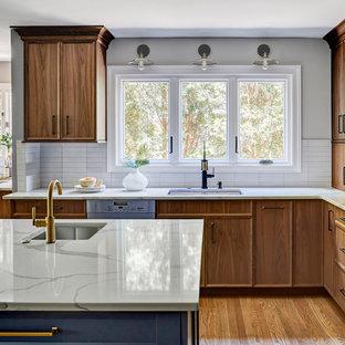 Offene, Große Moderne Küche in L-Form mit Unterbauwaschbecken, hellbraunen Holzschränken, Küchenrückwand in Weiß, braunem Holzboden, Kücheninsel, braunem Boden, flächenbündigen Schrankfronten, Quarzwerkstein-Arbeitsplatte, Rückwand aus Metrofliesen, Küchengeräten aus Edelstahl und weißer Arbeitsplatte in Chicago