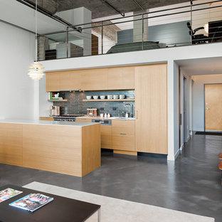 Imagen de cocina lineal, contemporánea, abierta, con armarios con paneles lisos, puertas de armario de madera clara, salpicadero verde, electrodomésticos con paneles y suelo gris