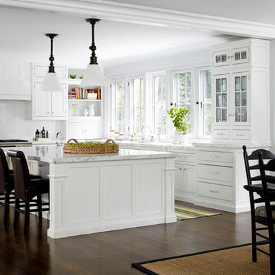 Inspiration for a mid-sized timeless l-shaped dark wood floor eat-in kitchen remodel in New York with white cabinets, white backsplash, subway tile backsplash, stainless steel appliances, an island and beaded inset cabinets