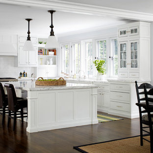 This is an example of a mid-sized traditional l-shaped eat-in kitchen in New York with recessed-panel cabinets, white cabinets, white splashback, subway tile splashback, stainless steel appliances, dark hardwood floors and with island.