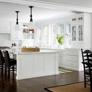 На фото: угловая кухня - столовая среднего размера в классическом стиле с фасадами с утопленной филенкой, белыми фасадами, белым фартуком, фартуком из плитки кабанчик, техникой из нержавеющей стали, темным паркетным полом и островом с